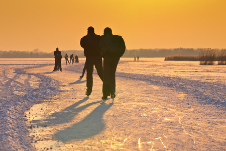winterday: Ice Skaters on frozen lake seen on their back under orange setting sun