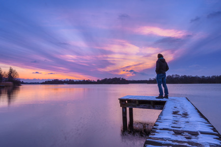 Man overthinking problems on pier during beautiful sunset in winter