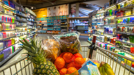 food products: Easter shopping Grocery cart at a colorful supermarket filled up with food products as seen from the customers point of view Stock Photo