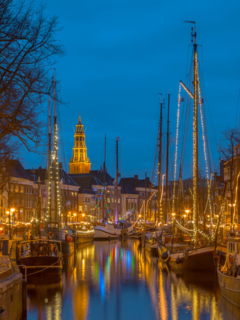 Historic sailing ships moored at river quay in Groningen city centre on the annual Winterwelvaart festival around christmas.