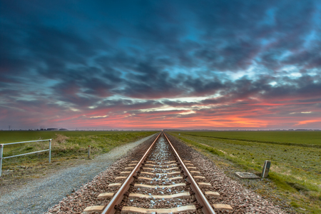 Dissapearing railroad on the horizon under a blue and red sky as a concept for future successfullness. Stock Photo