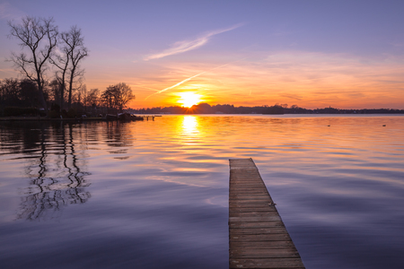 jetty: Tranquil purple Sunset over Serene Water of Lake Paterwoldsemeer, Netherlands Stock Photo