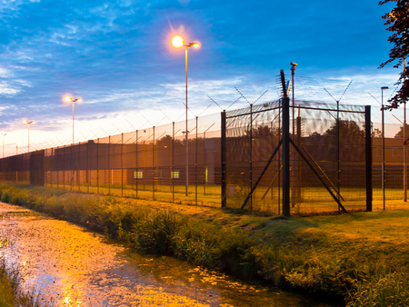 European Prison Fence with Ditch at Dawn Stock Photo