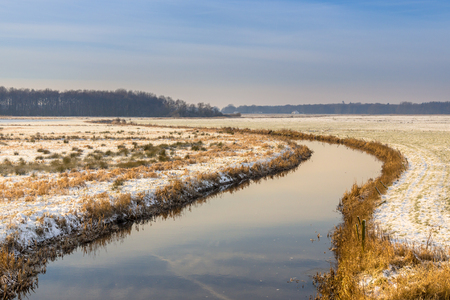 Lowland river winter landscape with thin layer of snow in Koningsdiep basin in the Netherlands