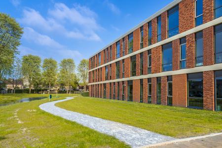 anuncio publicitario: Detalle de la configuración de la escuela situada junto al parque con pista de caminar en un día brillante en la primavera Foto de archivo