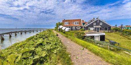 Typical fishing village houses in township rozewerf on Marken island Waterland, with icebreakers in the Ijsselmeer or formerly Zuiderzee, the Netherlands Stock Photo