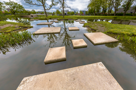 Labyrinth of Stepping stones in public pond of park as part of playground for children. Good training to improve locomotion skills and dexterity