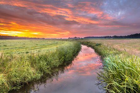 enlightment: Spiritual voyage concept  summer sunrise over lowland river Grootdiep near Oosterwolde, Friesland, Netherlands