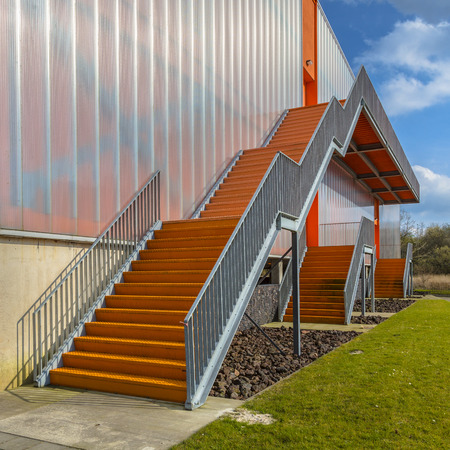 emergency stair: Modern emergency exit escape ladders on the exterior of an orange building facade Stock Photo