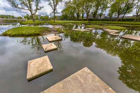restraints: Stepping stones in pond of public park as part of playground for children. Good training to improve locomotion skills and dexterity. Disability concept