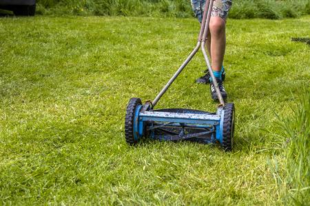 Schuif de gazonmaaier in actie. Door het gras door een jongen geduwd. Stockfoto - 72084646