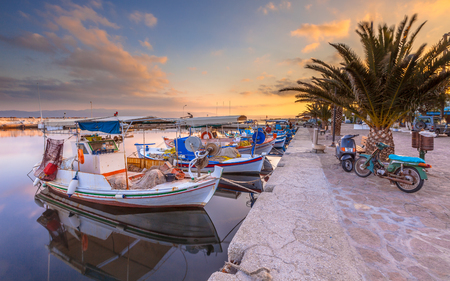 skiathos: Fishing harbor scene in Greece with boats, palm trees and scooters at sunrise on a beautiful tranquil summer day