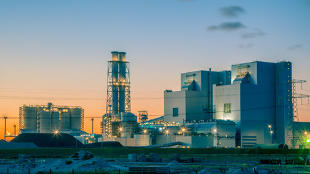 Ultra modern coal powered electrical power plant at sunset under a blue and orange sky