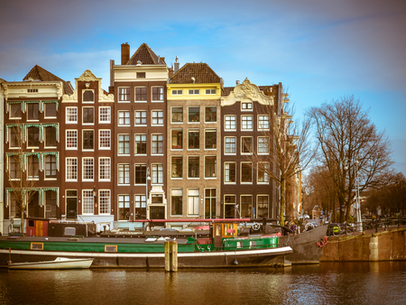 prinsengracht: Colorful traditional canal houses and boats in retro look. In the UNESCO World Heritage site of Amsterdam on the corner of Amstel and Nieuwe Prinsengracht Stock Photo