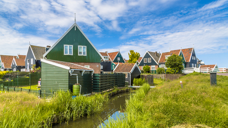 Traditional Dutch village scene with wooden houses and canal on the island of Marken in the Ijsselmeer or formerly Zuiderzee, the Netherlands