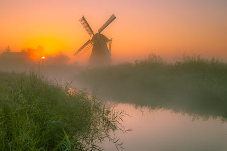 Dutch Traditional Windmill in a marshland area on a foggy morning in september