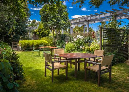 marlborough: Home backyard with modern garden table set in sunny a lush garden with shade of trees Stock Photo