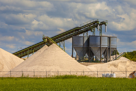 aggregates: Industrial sand mining terminal with conveyer belts and silos on a summer day