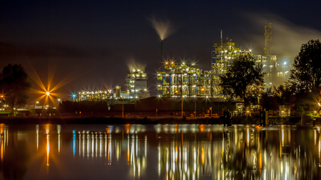 Nachtszene des Details eines schweren chemischen Industriegebiets mit den Rohren und den Lichtern, die im Wasser sich reflektieren