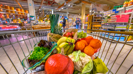 Grocery shop cart in supermarket filled up with fresh and healthy food products as seen from the customers point of view with people shopping in background Banque d'images