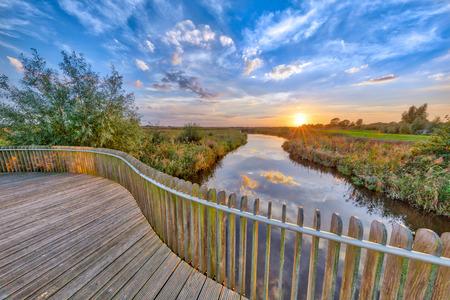 Vivid sunset over Wooden Balustrade balcony on bridge in Onlanden Nature reserve waterlogging area Groningen, Netherlands