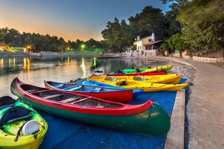 Colorful Kayaks for rent in a croatian bay at sunset under beatuful sky and lighting Editorial