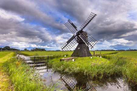 Traditional Wooden Windmill. This Historic water management pump device was used to drain water from a Polder, Netherlands Stock Photo - 75181583