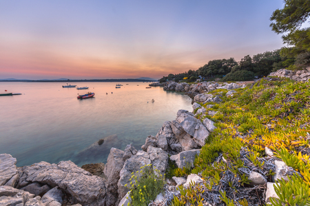 Croatian rocky touristic coast. Long exposure image of rocks, vegetation, and boats on the Island of Cres. Stock Photo