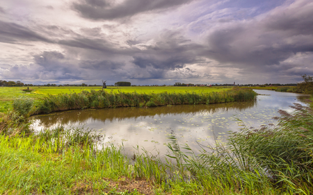 dutch: Typical Dutch Landscape with Meadows, River and Clouds Stock Photo
