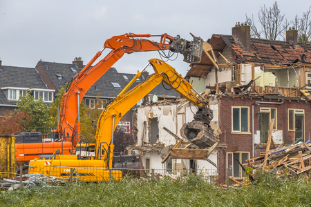 Two Demolition cranes demolishing old row of houses in the Netherlands Stock Photo