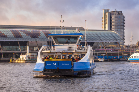 ferryboat: AMSTERDAM-DEC. 28, 2015. Ferryboat on Dec. 28, 2015 in Amsterdam. Several modern designed Ferryboats provide the 24h daily connection between Central Station and Buiksloterweg, crossing the river IJ. Editorial