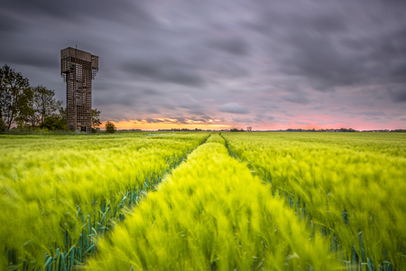 WARFHUIZENTHE NETHERLANDS - MAY 5th, 2015: Reminiscent of the cold war: An obsolete monumental air defence tower owned by a non-profit foundation overseeing a beautiful sunset over farm fields