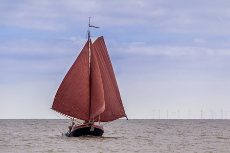 Traditional dutch flatbottom sailing boat on the wadden sea