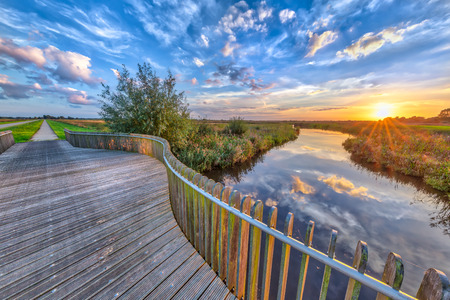 Tranquil vivid sunset over Wooden Balustrade balcony on bridge in Onlanden Nature reserve waterlogging area Groningen, Netherlands
