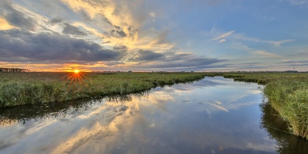 네덜란드에서 일몰에 습지대 자연 보호구에서 강 일몰