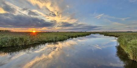 Tramonto sopra il fiume nella riserva naturale della regione paludosa al tramonto nei Paesi Bassi