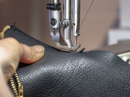 craftmanship: Sewing machine in a leather workshop in action with hands working on a shoulder bag Stock Photo