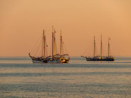Vintage Sailing Ships in Orange Light during Sunset over IJsselmeer, The Netherlands