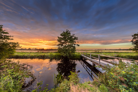 Wooden footbridge over river in dutch countryside near Groningen under amazing dark sunset during a sunday afternoon stroll