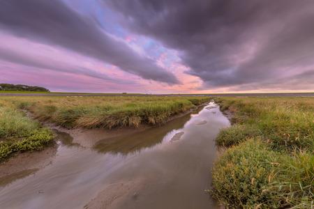 Sunset over graben creek in tidal marsh flat at Waddensea, Friesland, Netherlands Stock Photo