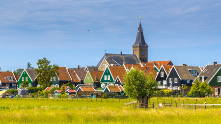 Church towering above Village with colorful wooden houses on the island of Marken in the Ijsselmeer or formerly Zuiderzee, the Netherlands