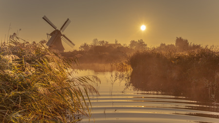Characteristic historic windmill in hazy wetland on a warm foggy september morning in the Netherlands Stock Photo