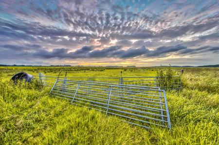 Metal gates in farmland field under setting sun with beautiful clouded sky