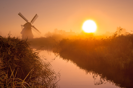 Characteristic historic windmill in a polder wetland on a foggy september morning in the Netherlands Stock Photo - 84640746