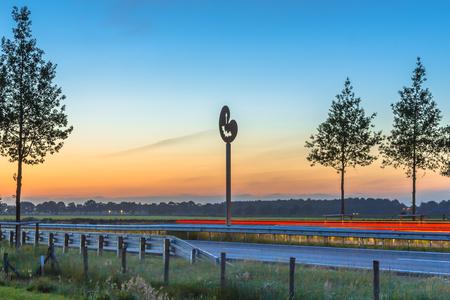 Drachten, Netherlands - June 9, 2016: Regional highway N381 at dusk with proven functional wildlife crossing hop over aids for bats and birds
