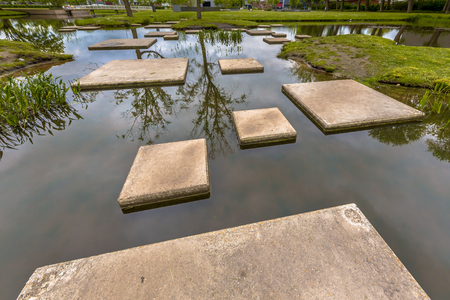 Concept for the difficulties disabled people will face in daily life. Labyrinth of Stepping stones in public pond of park as part of playground for children.