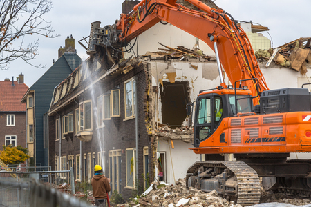 Orange Demolition crane demolishing old row of houses in the Netherlands
