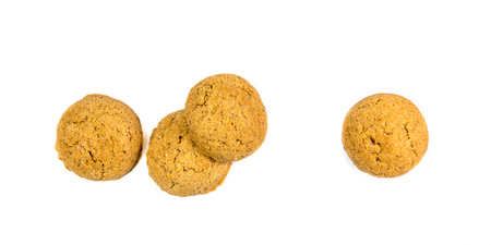 Four scattered ginger nuts in a row seen from above as Sinterklaas decoration on white background for dutch sinterklaasfeest holiday event on december 5th