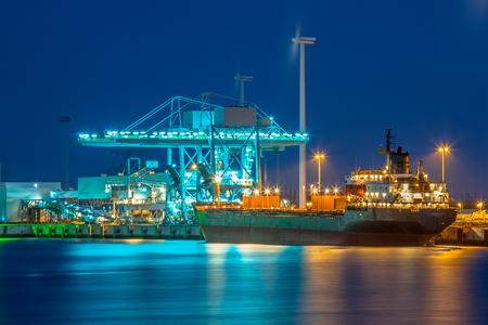 Het nautische schip op een kade tijdens schemering wordt leeggemaakt met reusachtige moderne kraanvogels onder kleurrijke verlichting Stockfoto