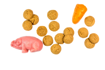 zwarte: Group of Pepernoten cookies with marzipan pig and carrot Sinterklaas decoration on white background for dutch sinterklaasfeest holiday event on december 5th